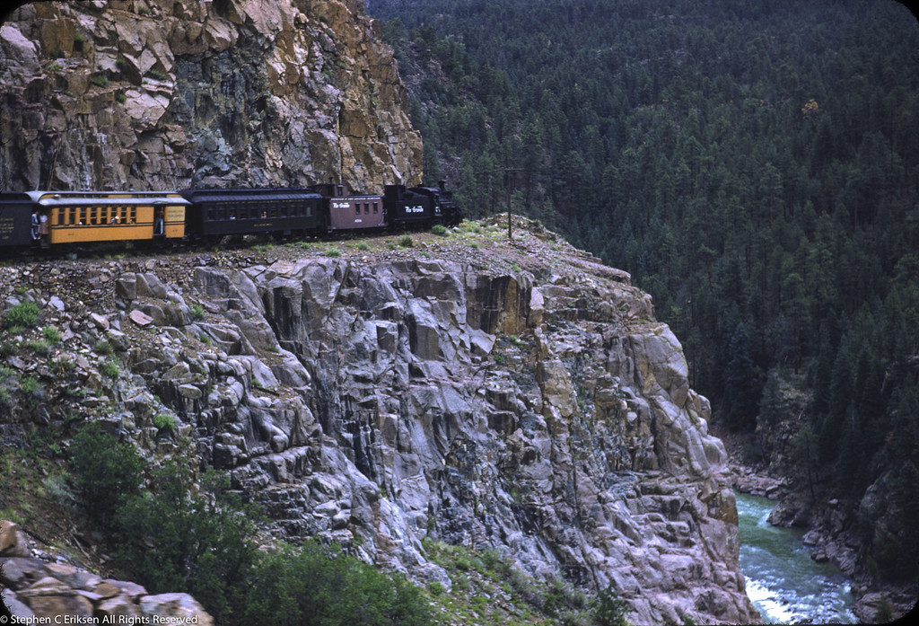 Classic 1950's highline view with the Silverton train in a mixed color scheme of Pullman green and Rio Grande gold.